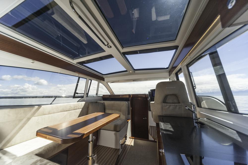 Skippers Reich: Der helle Decksalon mit Galley achtern und Esstisch, sowie den umkehrbaren Sitzen für Fahrer und Beifahrer. Foto: boats.com/Wanke