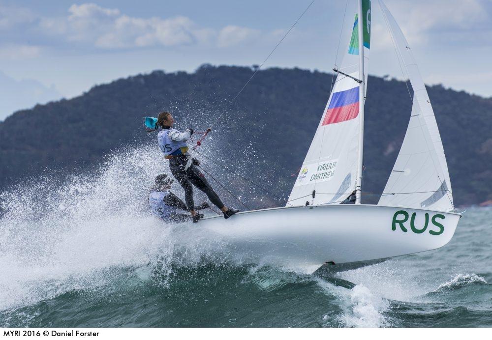 Eine olympische Zweimannjolle der 470er Klasse. Die Crew steht bei viel Wind im Trapez, um dem Boot Stabilität zu verleihen. Das Schwert unter dem Boot ist im Wellenkamm sichtbar. Foto: World Sailing/Daniel Forster