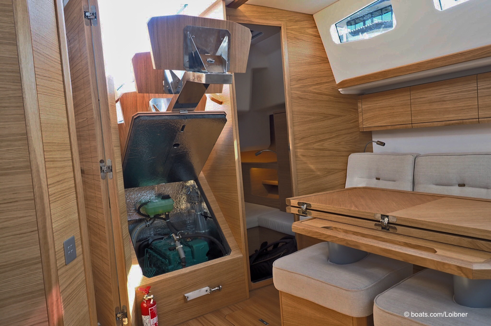 Zugang zum motor hinter der hochgeklappten Niedergangstreppe. Davor, rechts der absenkbare Salontisch mit den entfernbaren Hockern. Foto: boats.com/Loibner